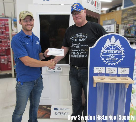 Man in blue shirt and man in black shirt receiving a check