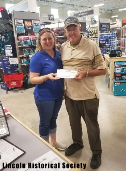 Woman in blue polo standing next to man in tan polo in hardware store